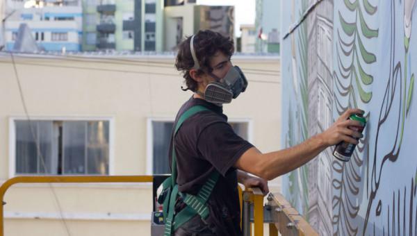 Artista Kelvin Koubik inicia graffiti em frente à Rua da Cultura