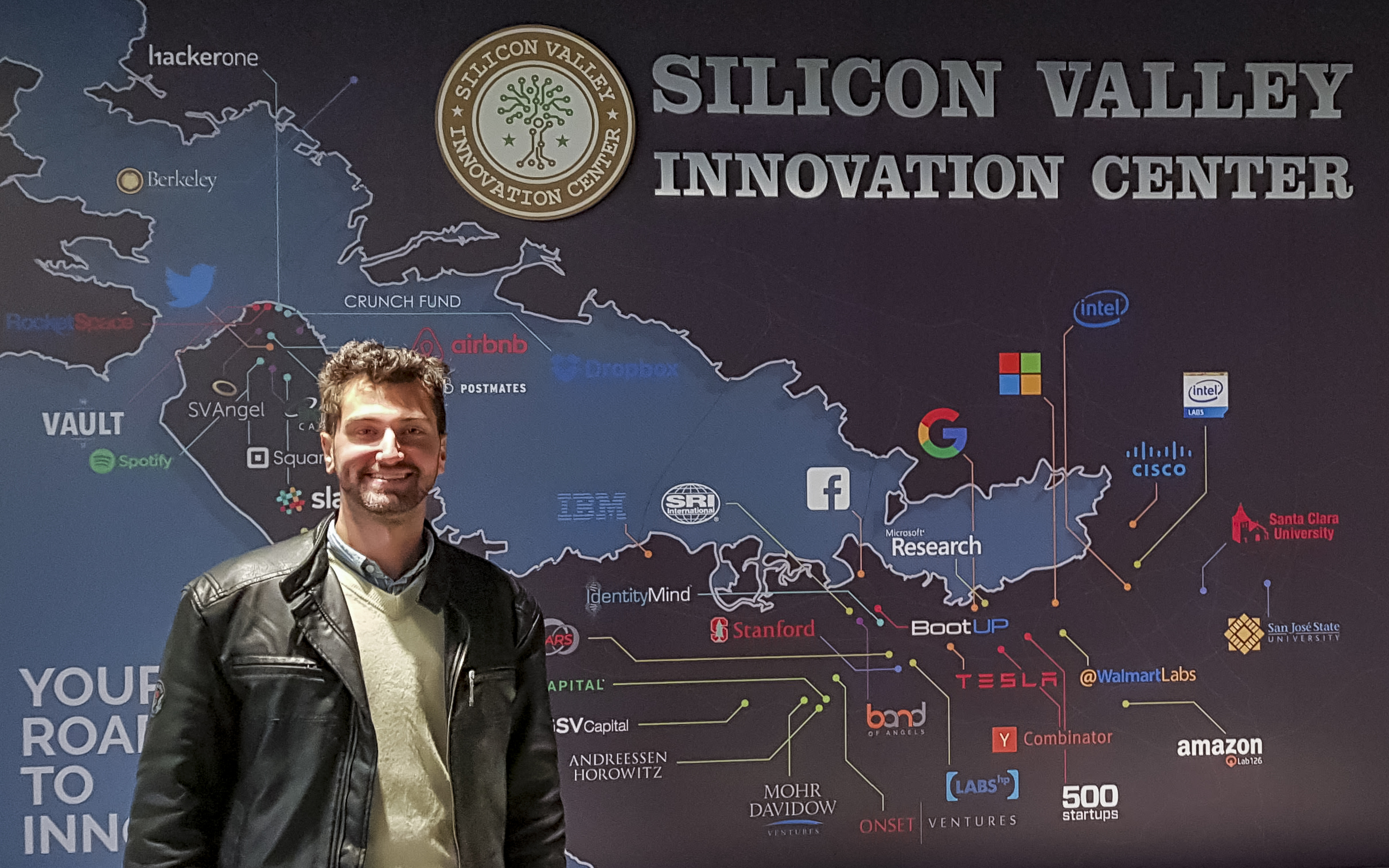 Estudante Giovani Righi em frente à mural de empresas do Vale do Silício