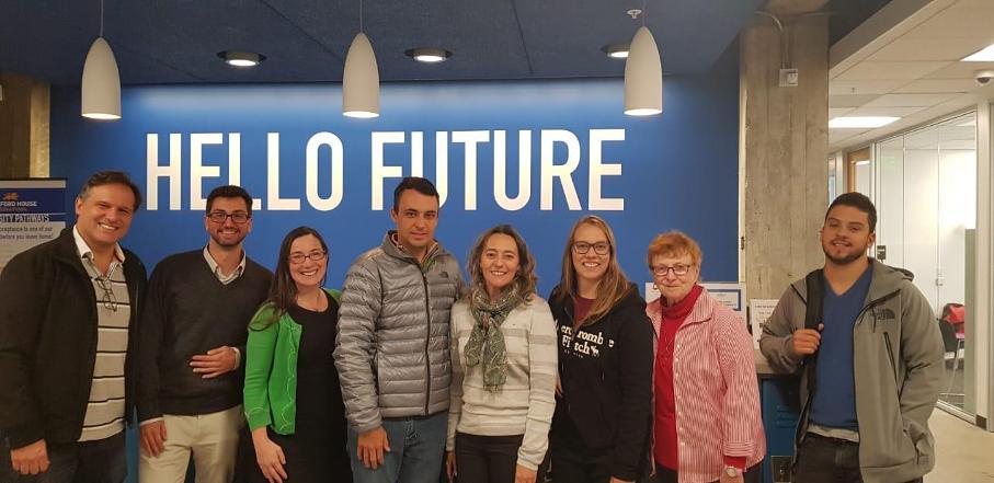 Alunos e professora da PUCRS em frente a mural que diz Hello future