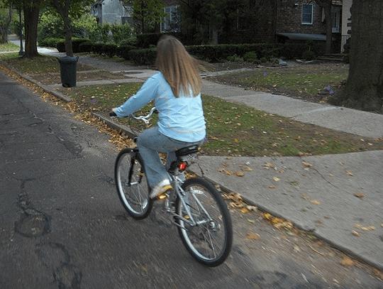 Uma garota andando de bicicleta na rua