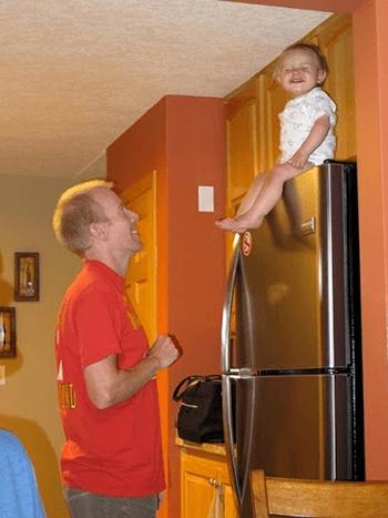 Um homem parado em frente a uma geladeira metálica com freezer e com um bebê sentado no topo