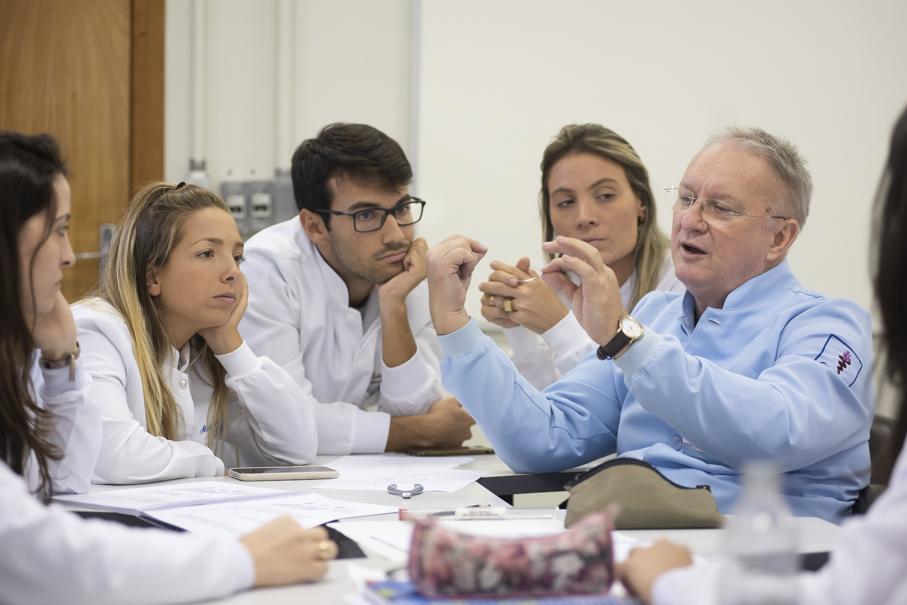 Professor Jose Nelson Mucha, sentado e rodeado por alunos, explica fundamentos da ortodontia