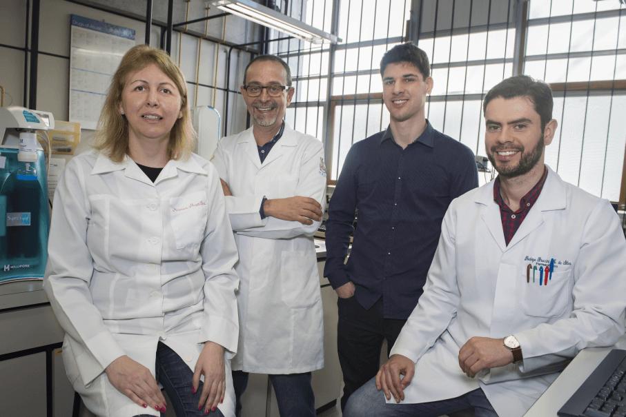 Pesquisadores Maria Martha Campos, André Arigony Souto, Filipe D'Jacques e Rodrigo Braccini, vestindo jaleco em um laboratório da PUCRS