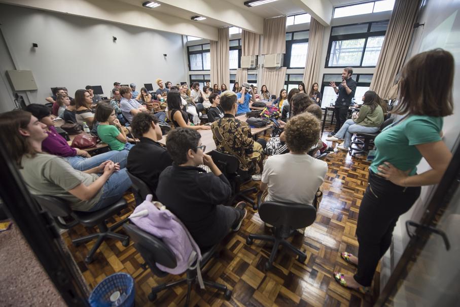 alunos acompanham atividades de boas-vindas. sala de aula cheia de alunos virados para trás
