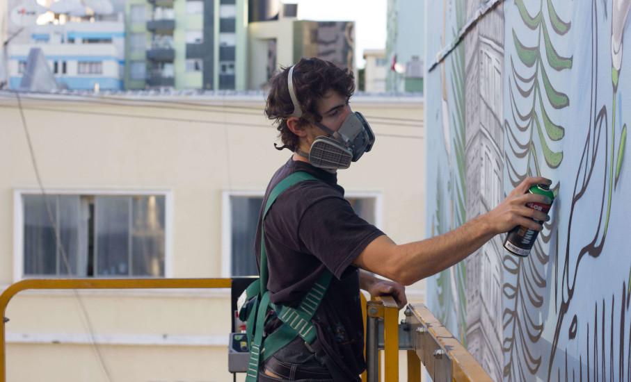 Artista visual Kelvin Koubik pintando mural