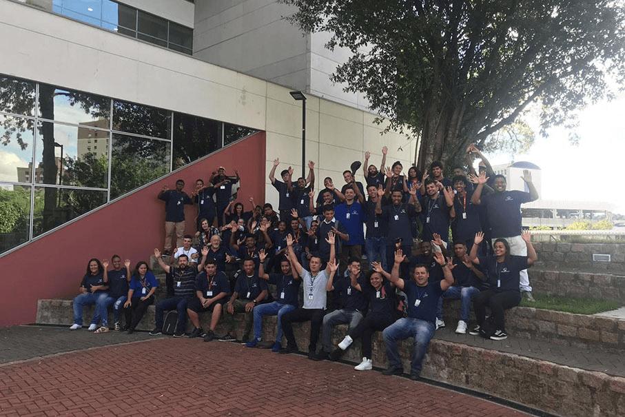 Grupo de alunos da Fundação Pão dos Pobres em arena ao ar livre no Tecnopuc