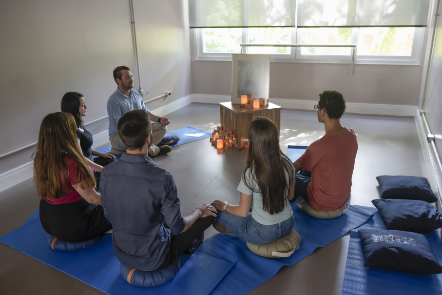 Pessoas em semi-círculo na sala de meditação