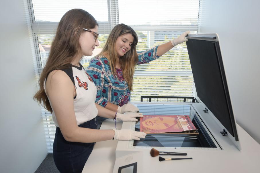 Duas estudantes digitalizam exemplar de jornal antigo